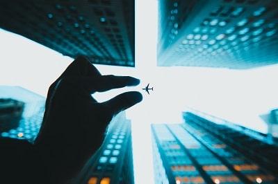 Wirtschaft und Corona. Symbolbild für den Versuch, etwas Großes (ein Flugzeug) mit zwei Fingern zu fassen